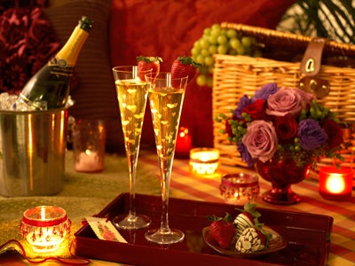 Champage setting with candles, flowers and fruit gift basket